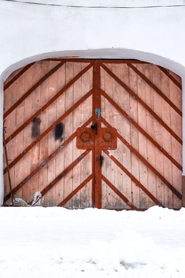 Gammal stor dörr Ingång med en välvd dubbel dörr som göras från trä med metallramen royaltyfri bild