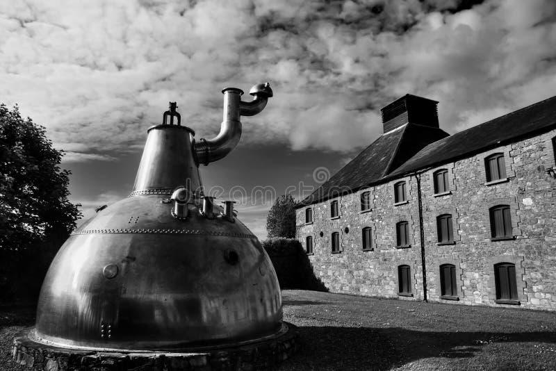 Gammal stor kopparwhiskyspritfabrik på stenfundament arkivfoto