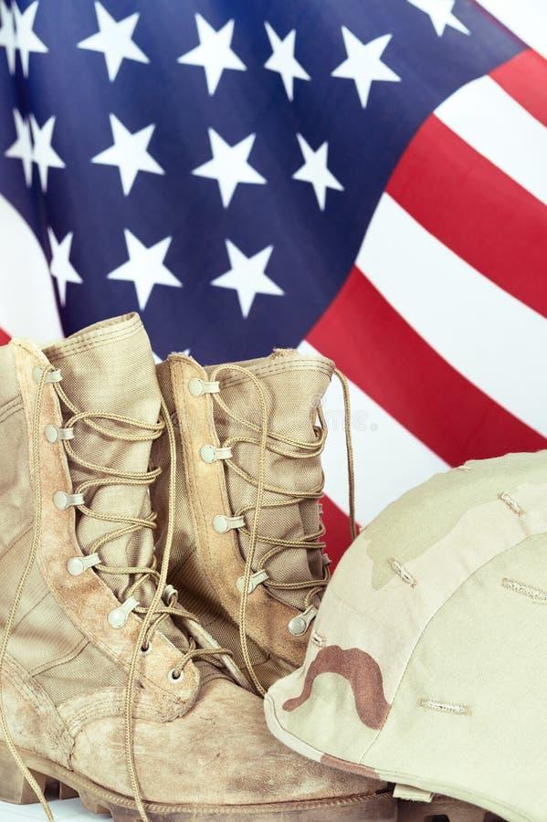 Gammal stridkängor och hjälm med amerikanska flaggan arkivbild