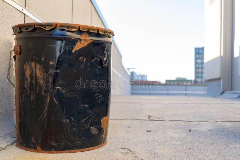 Gammal svart metallhink, buckligt & rostigt, på ett New York City tak, Bronx, NY arkivbilder