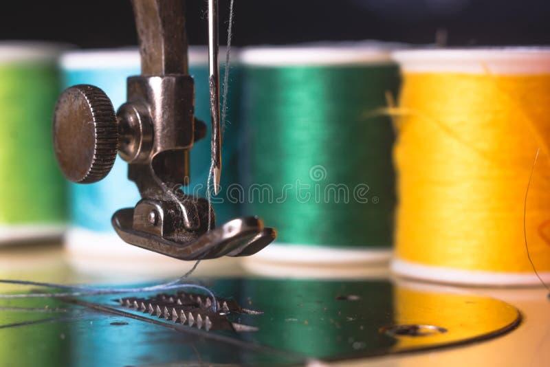 Gammal symaskin med den färgtråden och visaren, på en gammal grungy arbetstabell Tabell för arbete för skräddare` s textil eller  arkivbilder