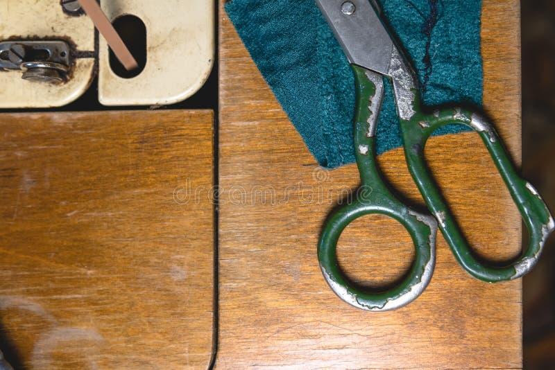 Gammal symaskin med sax, på en gammal grungy arbetstabell Tabell för arbete för skräddare` s textil eller fin torkdukedanande ind fotografering för bildbyråer