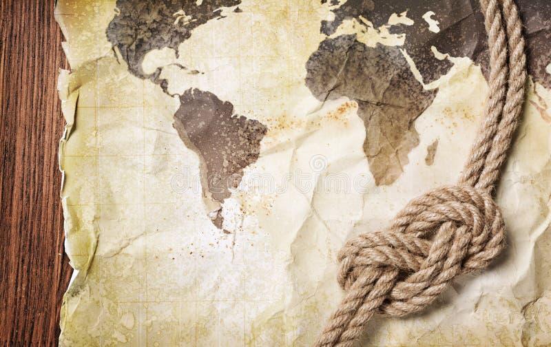Gammal tappningöversikt av världen på gult retro nedfläckat papper med fnuren av repet fotografering för bildbyråer