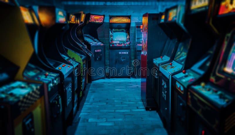 Gammal tappning Arcade Video Games i ett tomt mörkt spela rum med blått ljus med glödande skärmar och härlig retro design arkivbilder
