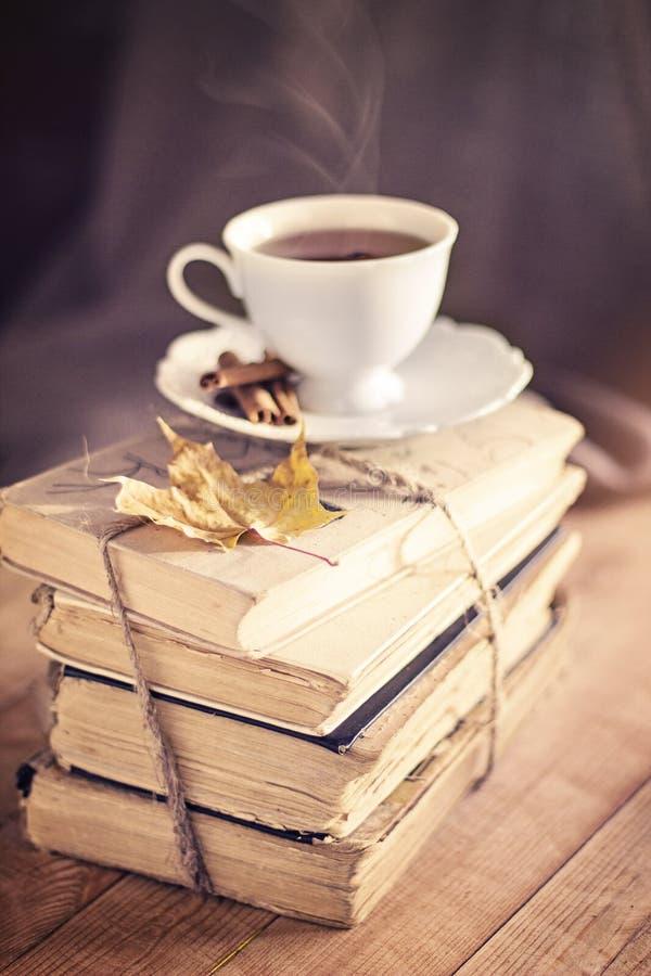 Gammal tappningböcker och kopp på trätabellen arkivbild