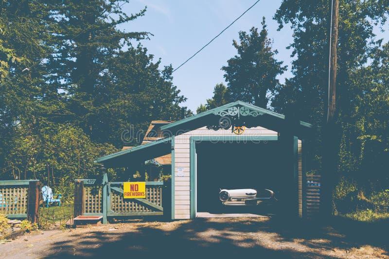 Gammal tappningbil som parkeras i ett litet garage bredvid ett tecken på ett staket som läser arkivbild