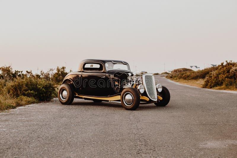 Gammal tappningbil som parkeras i mitt av motorvägvägen royaltyfri foto