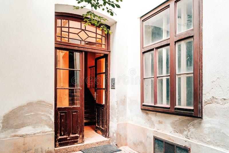 Gammal tappningborggård med den öppna ingångsdörren och trappuppgång i Wien royaltyfri fotografi
