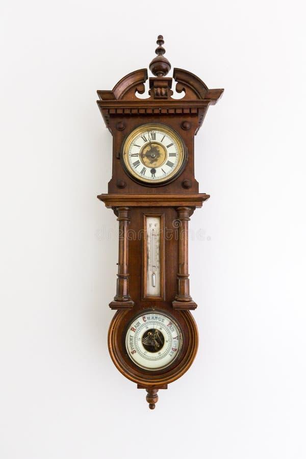 Gammal tappningklocka med barometern som isoleras på den vita väggen royaltyfria bilder