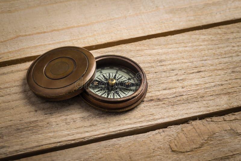 Gammal tappningkompass på tabellen royaltyfria bilder