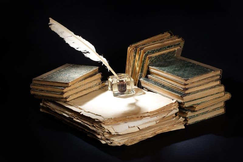 Gammal tappningreservoarpenna, böcker och bläckhorn på en svart bakgrund arkivfoton
