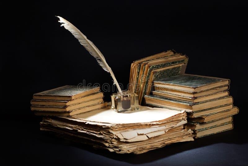 Gammal tappningreservoarpenna, b?cker och bl?ckhorn p? en svart bakgrund arkivbilder
