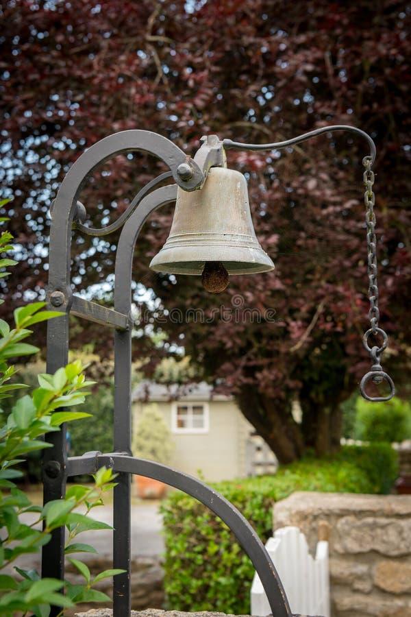 Gammal tappningringklocka på en trädgårdingång arkivfoton