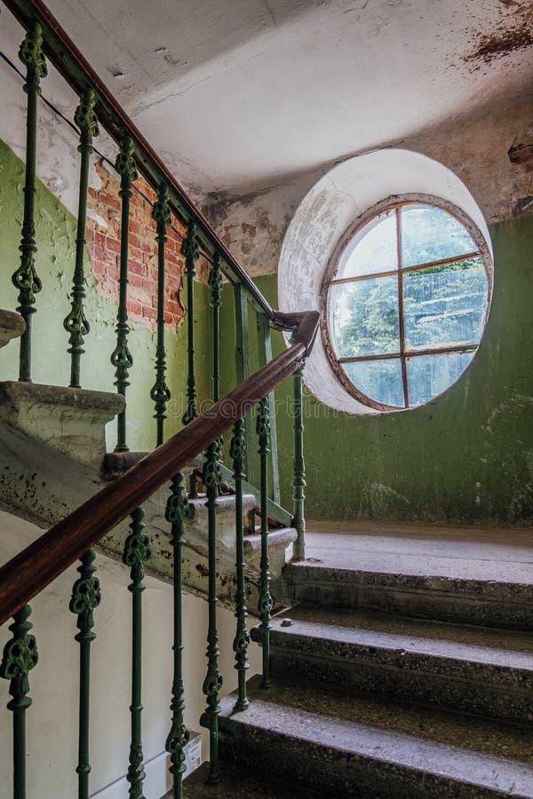 Gammal tappningtrappuppgång på det gamla huset ovalt fönster royaltyfri fotografi