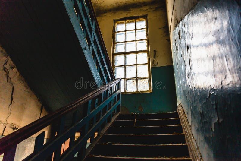 Gammal tappningtrappuppgånginre i smutsig övergiven byggnad för mörker arkivfoto