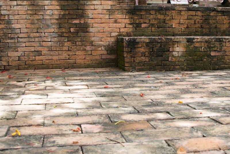 Gammal tegelstenbakgrund, ljus - apelsin i templet royaltyfri foto