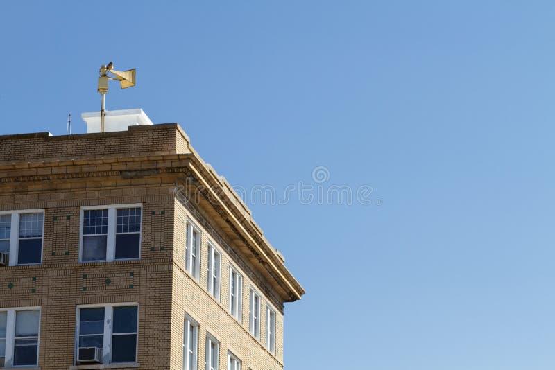 Gammal tegelstenbyggnad och siren för borgerligt försvar royaltyfri fotografi