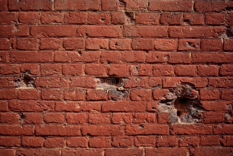 Gammal tegelstenvägg för bakgrund med hål av kulor arkivbilder