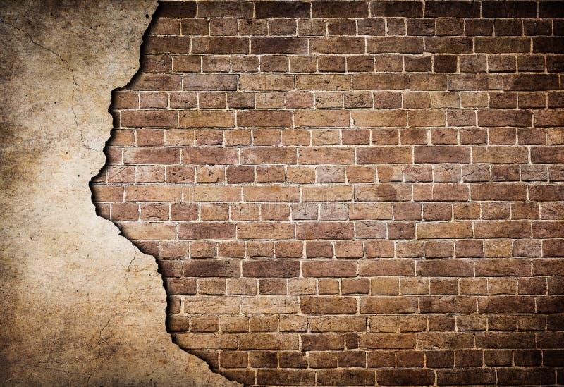 Gammal tegelstenvägg med den delvist skadade stuckaturen royaltyfri fotografi