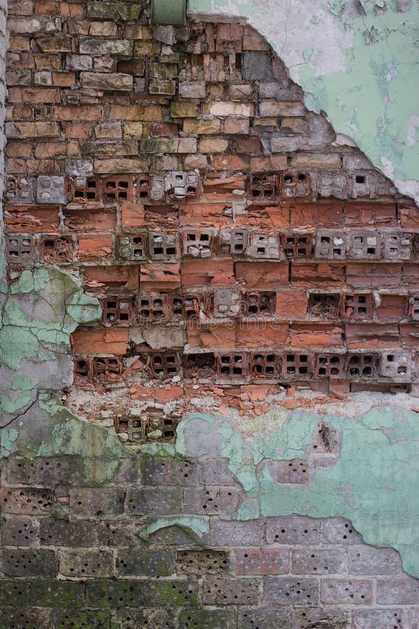 Gammal tegelstenvägg med sprucken målarfärg och murbruk arkivbild