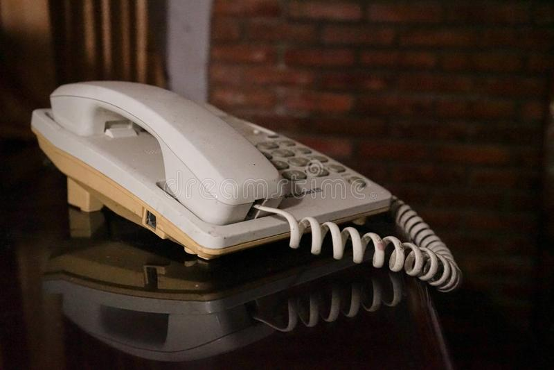 Gammal telefon i hus för tegelstenvägg arkivbilder