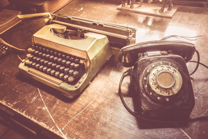Gammal telefon och typförfattare på skrivbordet royaltyfria bilder