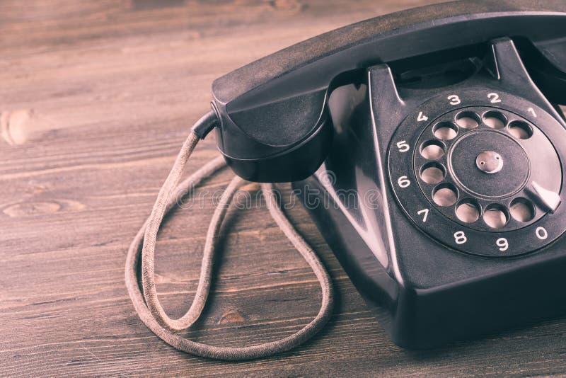 Gammal telefon på trätabellcloseupen arkivfoton