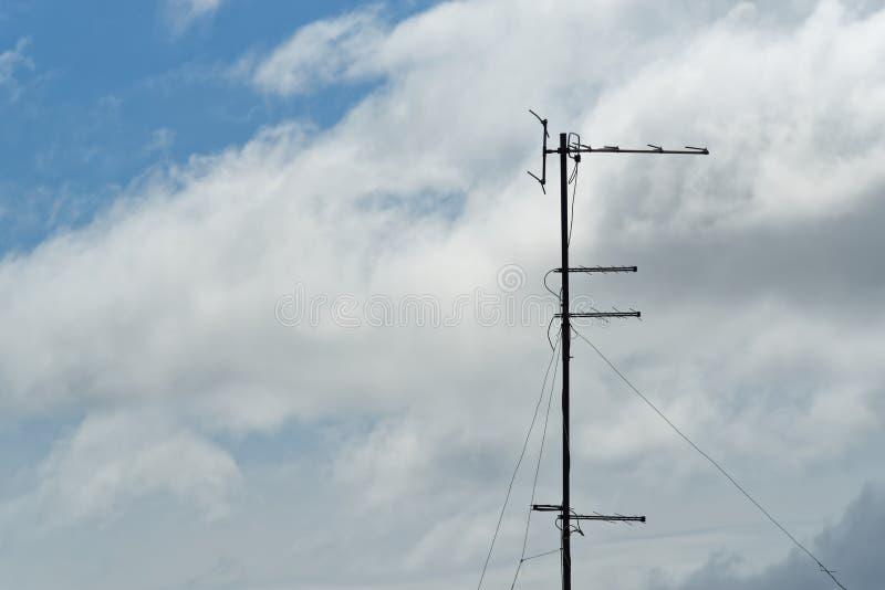 Gammal televisionantenn mot molnig himmel royaltyfria bilder