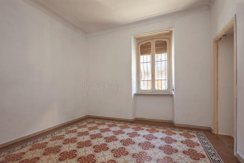 Gammal tom ruminre med det belade med tegel dekorerade golvet arkivbilder