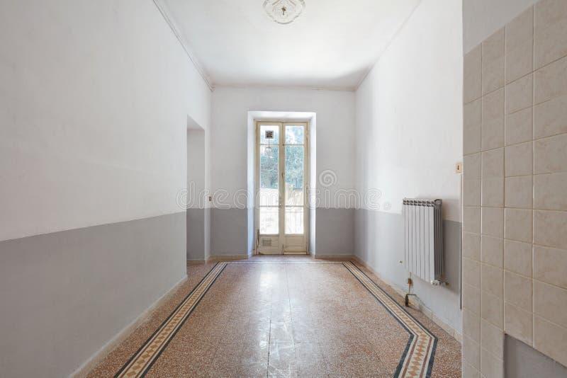 Gammal tom ruminre med fönstret och belagt med tegel golv arkivfoto
