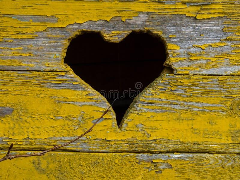 Gammal träbakgrund av bräden med sprucken och skalande målarfärg med formad hjärta arkivfoto
