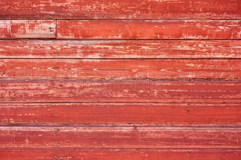 Gammal träbakgrund som målas med röd målarfärg med en textur av sprickor och skrapor arkivfoto