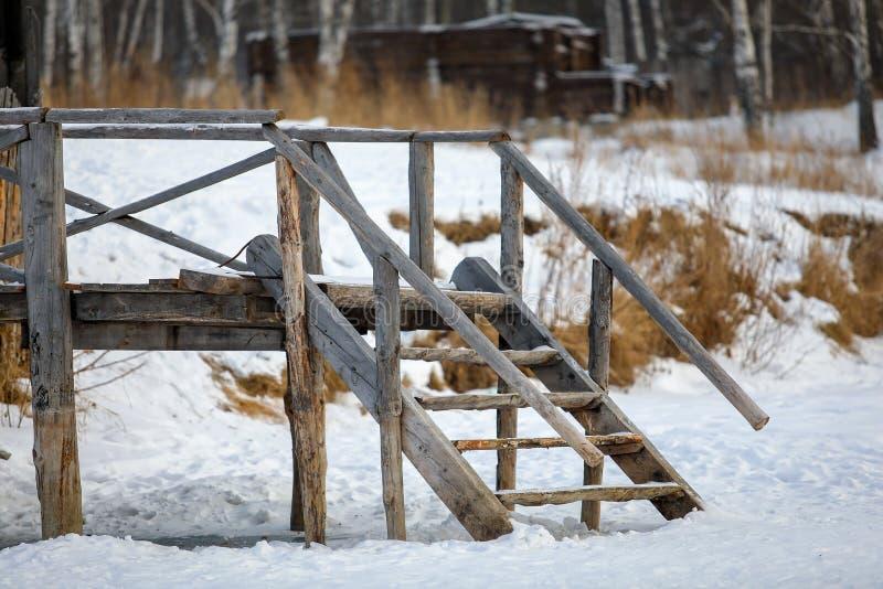 Gammal träbro, ingången till floden i vintern, slut upp fotografering för bildbyråer