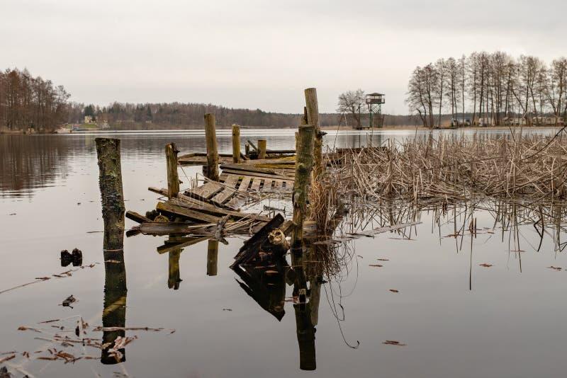 Gammal träbruten fiska bro Inaktivt ställe för att fiska på sjön royaltyfri bild