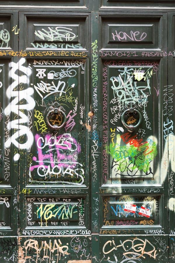 Gammal trädörr som täckas med grafitti i det Trastevere området Rome, royaltyfria bilder
