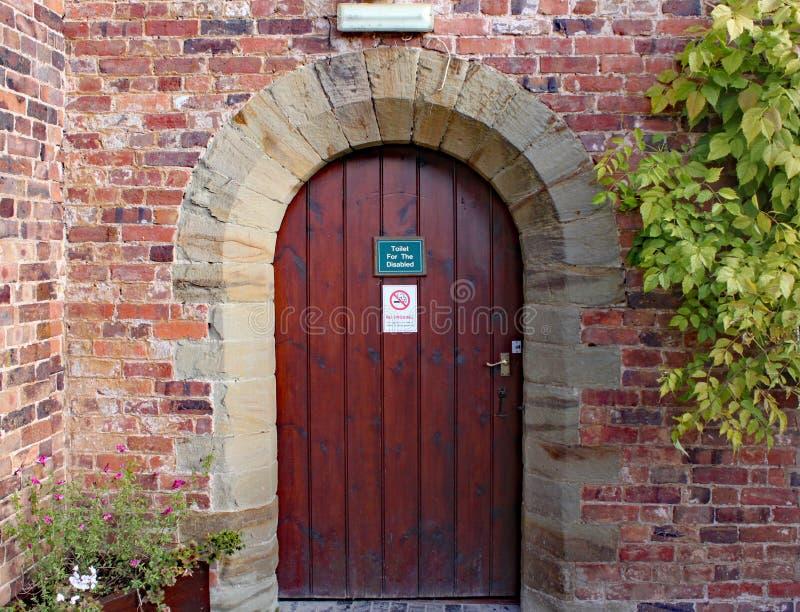 Gammal trädörr till rörelsehindrade toaletter på den Arley arboretumen i Midlands i England royaltyfria foton