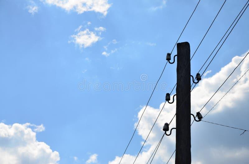 Gammal träelektrisk pol för överföring av bunden elektricitet på en bakgrund av en molnig blå himmel Föråldrad metod av att lever arkivfoto