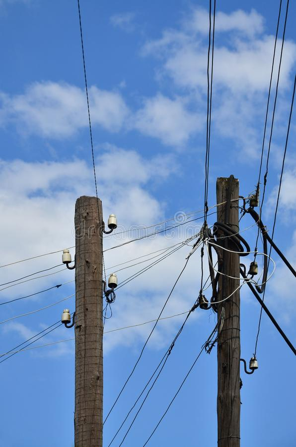 Gammal träelektrisk pol för överföring av bunden elektricitet på en bakgrund av en molnig blå himmel Föråldrad metod av att lever arkivfoton