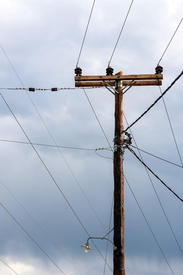 Gammal träelektrisk stolpe mot stormig himmel arkivfoton