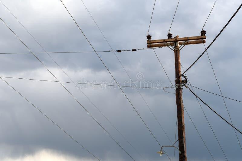 Gammal träelektrisk stolpe mot stormig himmel arkivbild
