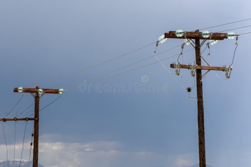 Gammal träelektrisk stolpe mot stormig himmel arkivfoto