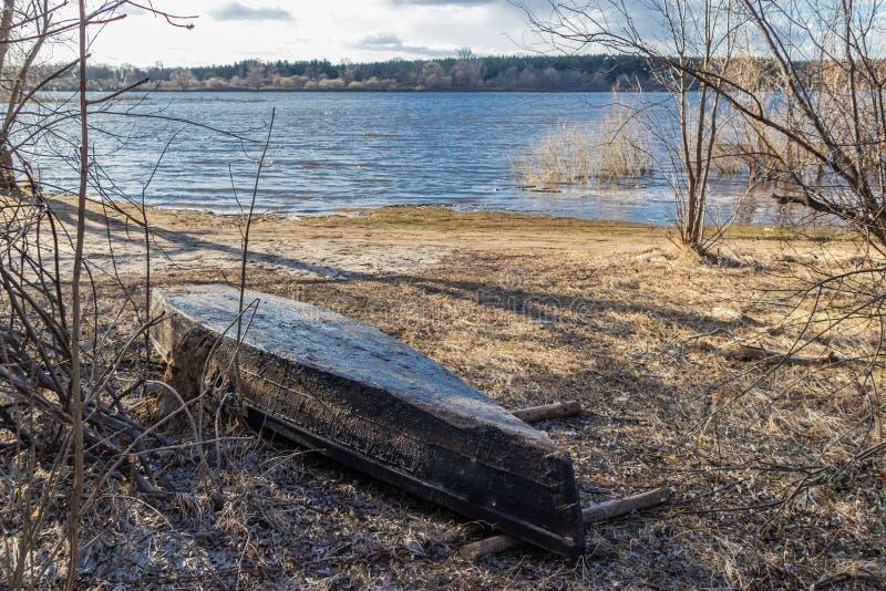Gammal träfiskebåt på flodbanken som väntar på säsongen av navigering royaltyfri fotografi