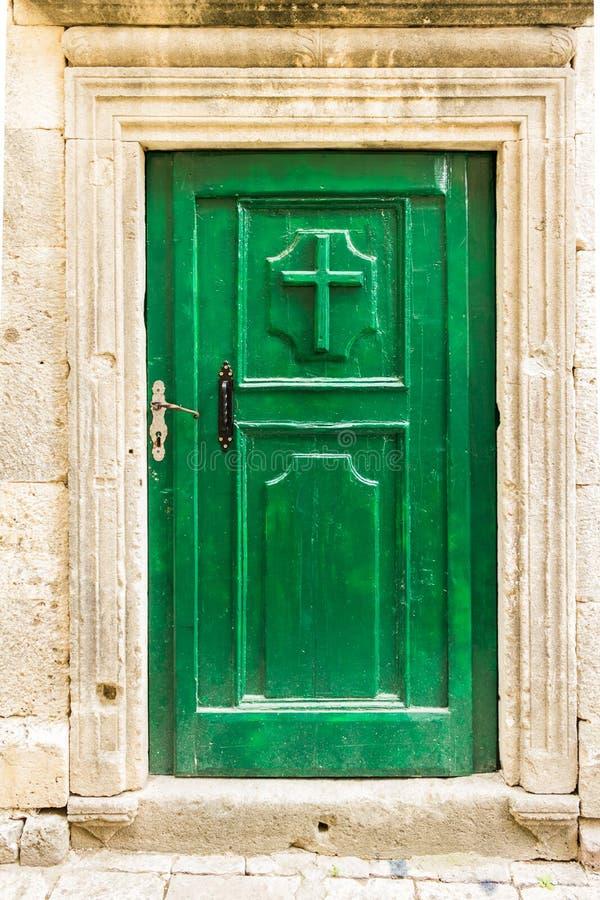 Gammal trägrön dörr med kristenkorset i Kotor, Montenegro arkivbilder