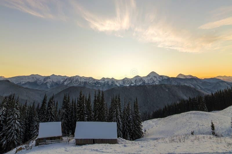 Gammal trähus, koja och ladugård i djup snö på bergdalen, prydlig skog, träig kullar på klar blå himmel på soluppgångkopieringsut arkivfoton
