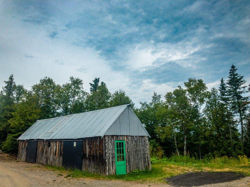 Gammal trähydda med den gröna dörren fotografering för bildbyråer