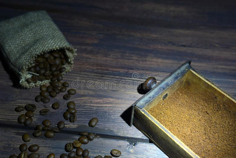 Gammal träkaffekvarnask med den lilla påsen på tabellen royaltyfri fotografi