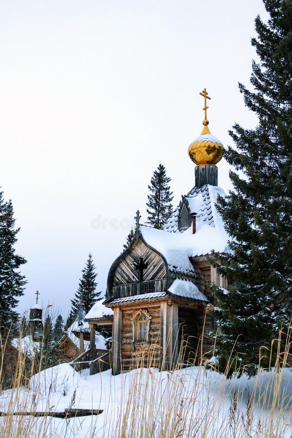 Gammal träkyrka med Golden Dome och kors i vinterdag arkivfoton