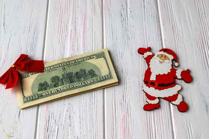 Gammal träljus julbakgrund med en bunt av dollar, roliga santa diagram och en röd pilbåge Gåvor för det nya året, ferie arkivbilder