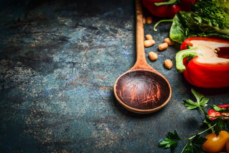 Gammal träsked och nya grönsaker för smaklig strikt vegetarianmatlagning på lantlig bakgrund, slut upp arkivbild