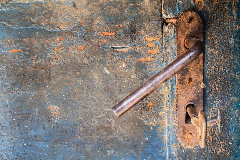 Gammal träsprucken dörr med låset och tangent för järn det rostiga royaltyfri bild